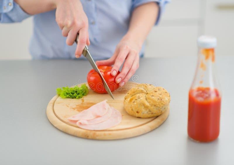 在做三明治的少妇的特写镜头在厨房里 库存图片
