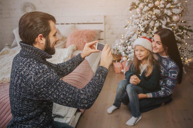 在做与智能手机的圣诞节大气的微笑的年轻家庭照片 免版税库存照片