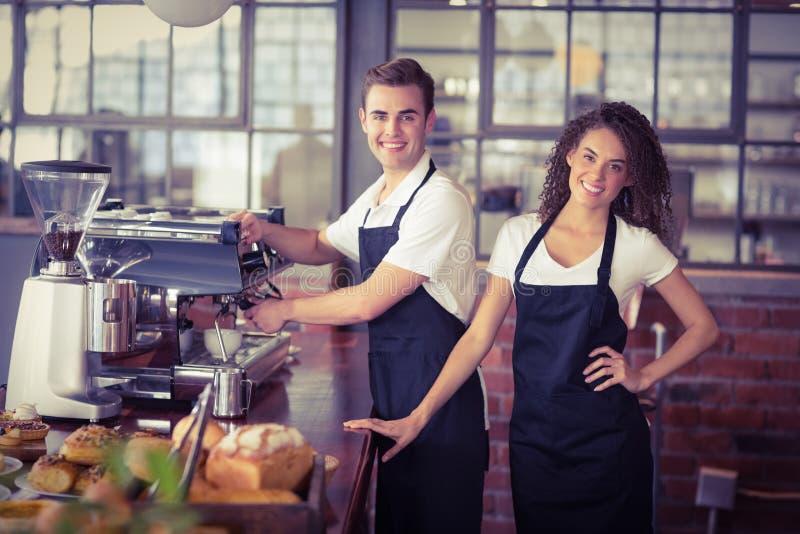 在做咖啡的同事前面的微笑的女服务员 库存图片