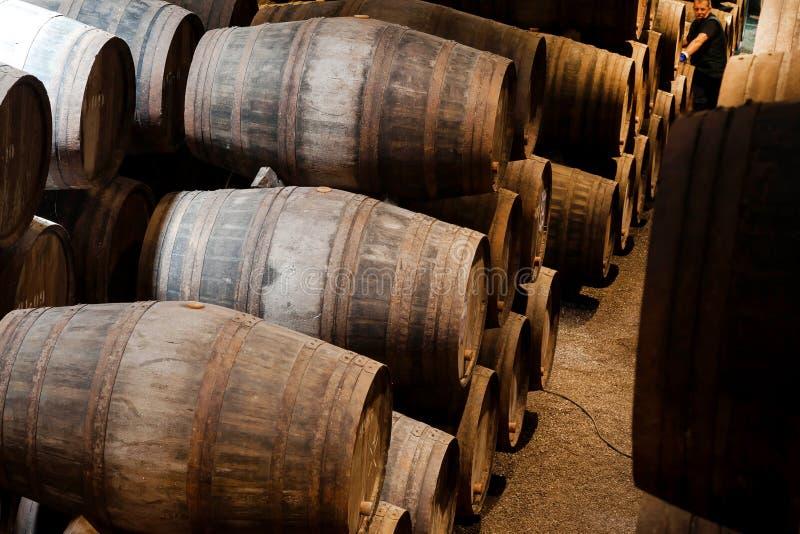 在做在葡萄酒酿造传统风格的老酿酒厂裁缝的和工作者里面的木桶波尔图酒  免版税库存图片