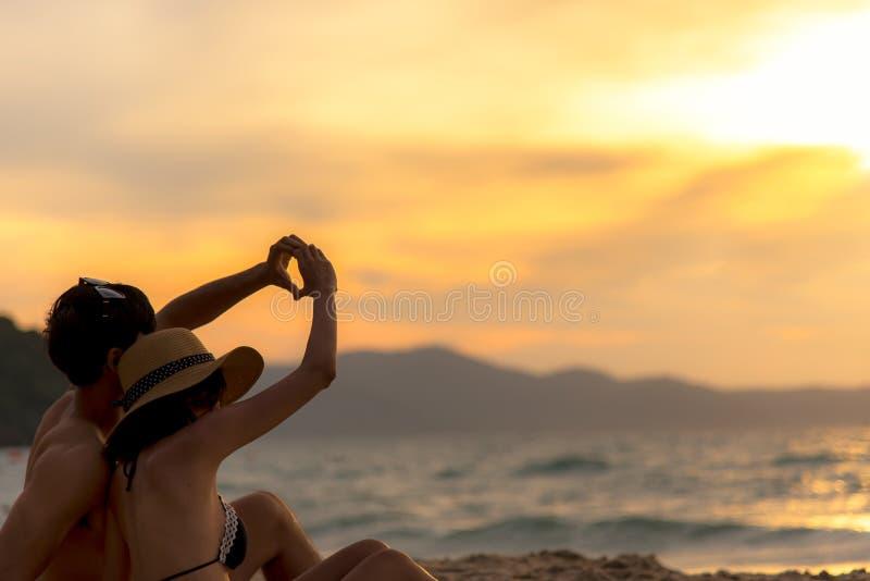 在做心脏的爱的夫妇-塑造用在热带的手在日落海滩在假日 免版税库存照片