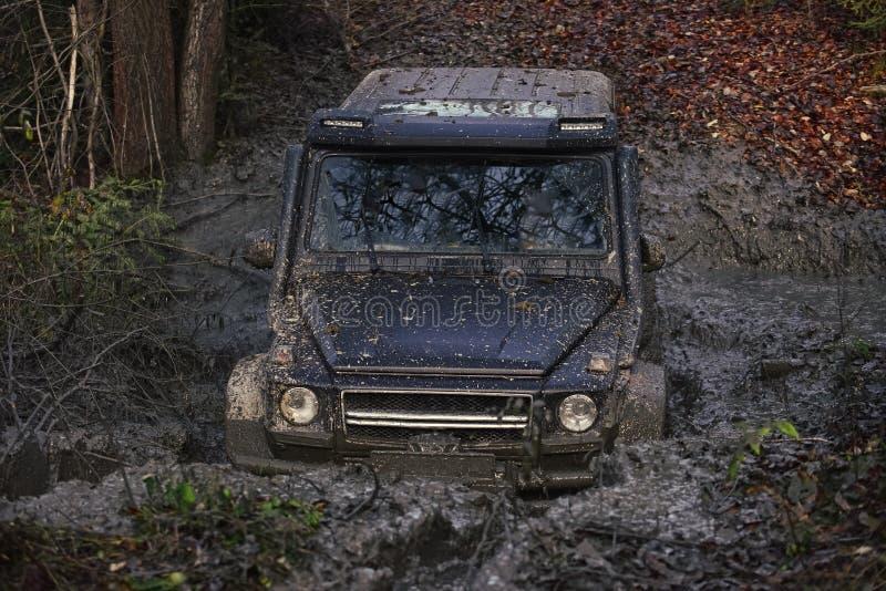在做泥的水坑的SUV飞溅 免版税库存照片