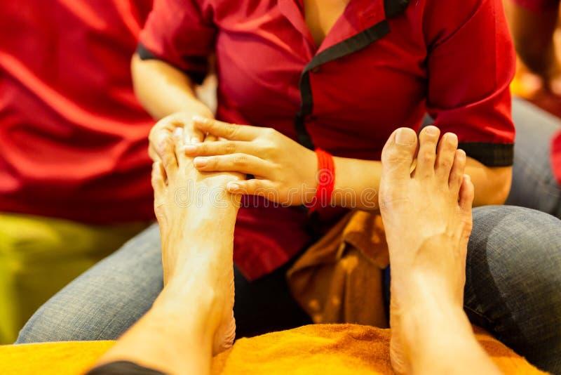 在做脚按摩的旅游脚的选择的焦点手 在柬埔寨在晚上 图库摄影