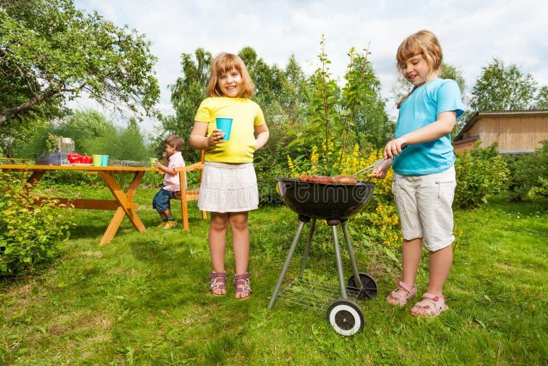 在做BBQ的格栅附近的两个女孩在庭院里 库存图片