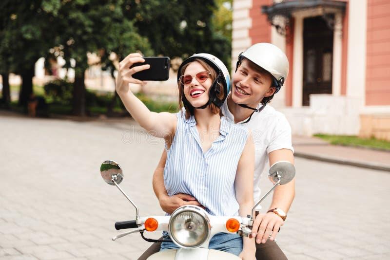 在做selfie的安全帽的快乐的年轻夫妇在智能手机 库存照片