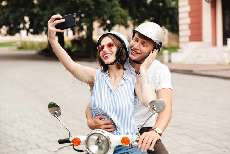 在做selfie的安全帽的愉快的年轻夫妇在智能手机 库存图片
