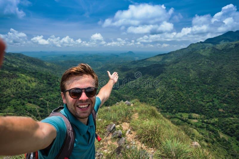 在做selfie的山顶部的白种人人在俏丽的风景背景  免版税库存图片