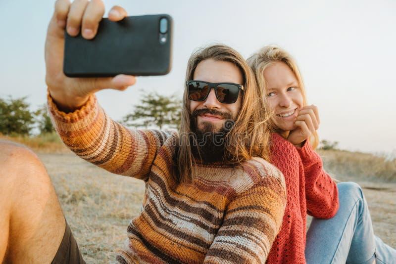 在做selfie的毛线衣的行家夫妇户外 免版税库存照片