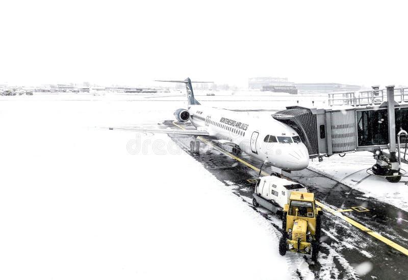 在停放的位置的蒙特内哥罗航空飞机在贝尔格莱德机场在寒冷冬天 免版税库存图片