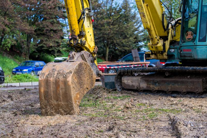 在停放的汽车之间的修路挖掘机在拥挤的街上 免版税库存照片
