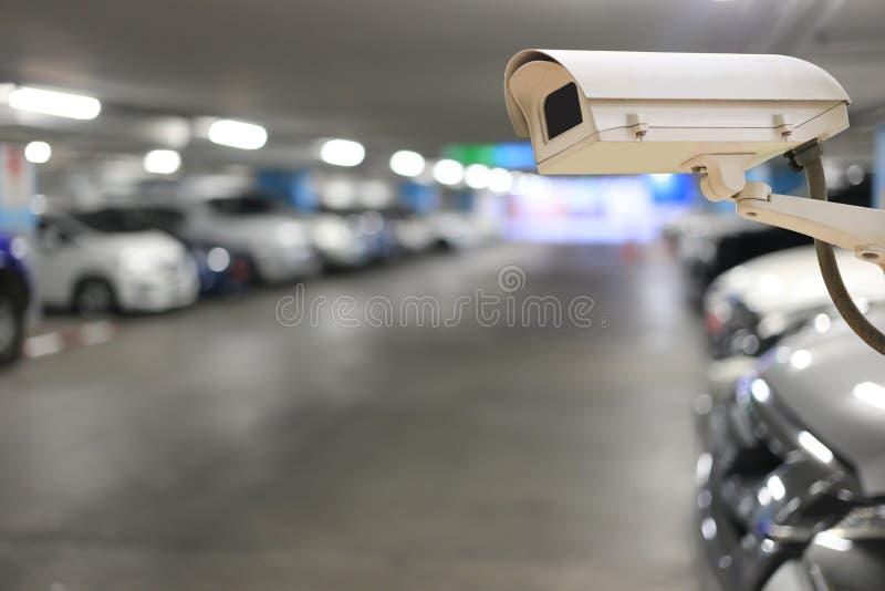 在停放被弄脏的汽车和bokeh光的CCTV照相机 免版税图库摄影