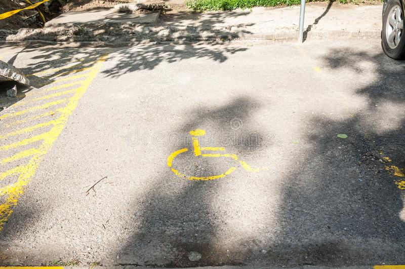 在停车场的有残障的残疾象标志或空白区在城市街道的停车场 免版税库存照片