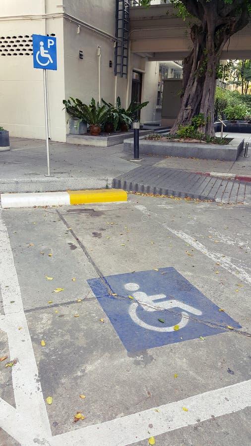 在停车处户外汽车标志的蓝色障碍为残疾,轮椅或者更旧老或者不能自助人 免版税库存照片