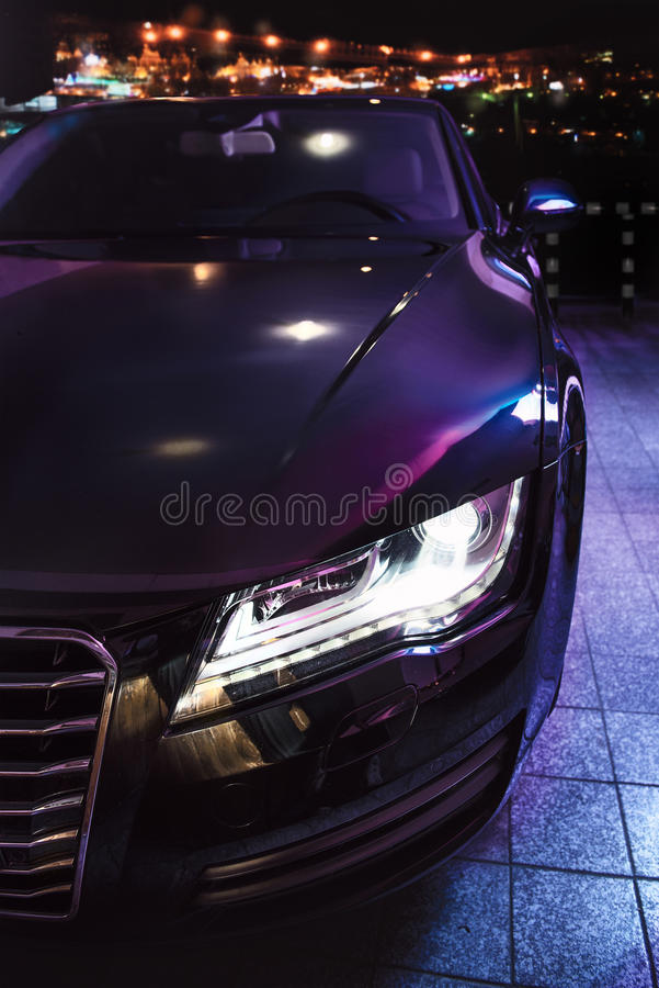 在停车处的豪华汽车在夜城市前面 免版税库存图片