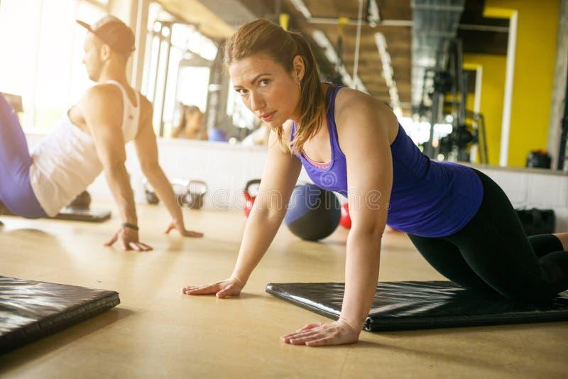 在健康俱乐部的两青年人锻炼 执行人俯卧撑 库存照片