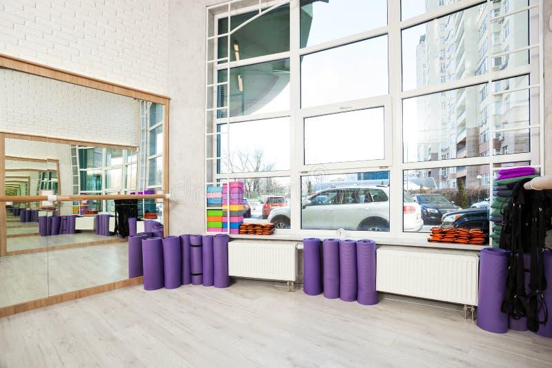 在健身俱乐部、白色砖墙、自然木地板和大窗口,现代顶楼演播室的空的空间,滚动了瑜伽席子,comf 库存照片