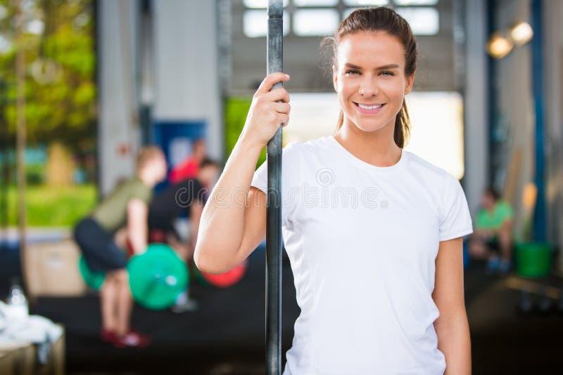 在健身俱乐部的微笑的女运动员佩带的白色T恤杉 图库摄影