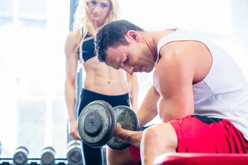 在健身健身房的夫妇与练习举重的哑铃 库存照片