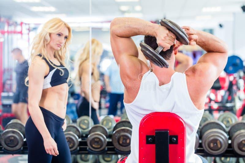 在健身健身房的夫妇与练习举重的哑铃 图库摄影