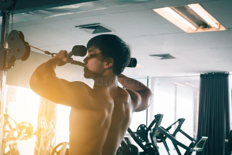 在健身房和做引体向上的亚洲人训练 免版税库存图片