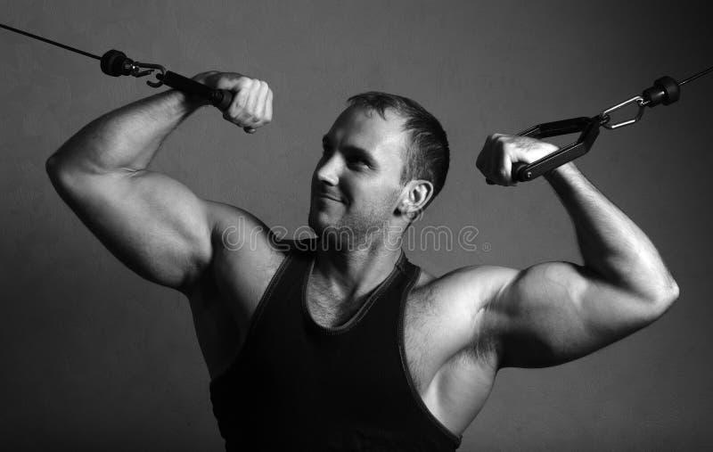 在健身房天桥的爱好健美者训练 图库摄影