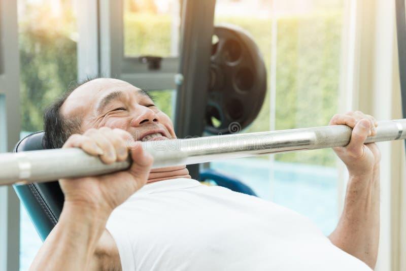 在健身房的亚洲老人举的杠铃 免版税库存照片