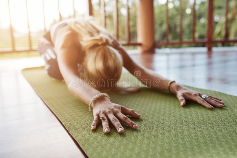 在健身房的健身女性执行的balasana瑜伽 库存照片