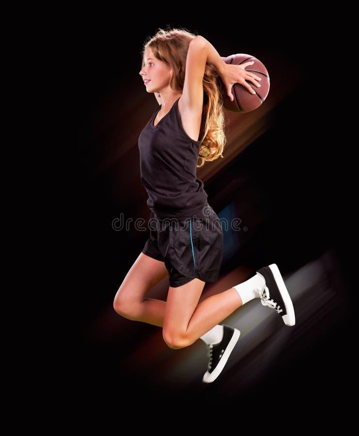 在健身房的女孩投掷的篮球 免版税库存照片