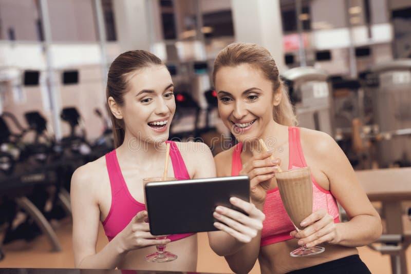 在健身房的妇女和女孩饮用的蛋白质震动 他们看起来愉快,时兴和适合 库存图片
