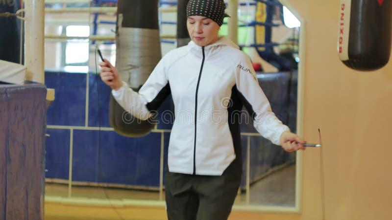 在健身房的妇女训练,与一条绳索的工作,在一个健康身体健身kickboxer系列之外 免版税图库摄影