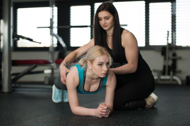 在健身房的妇女锻炼与她的做背部锻炼的教练 免版税库存图片