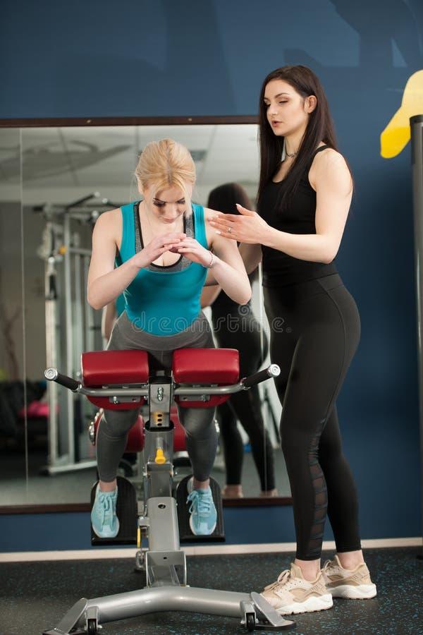在健身房的妇女锻炼与她的做背部锻炼的教练 库存图片