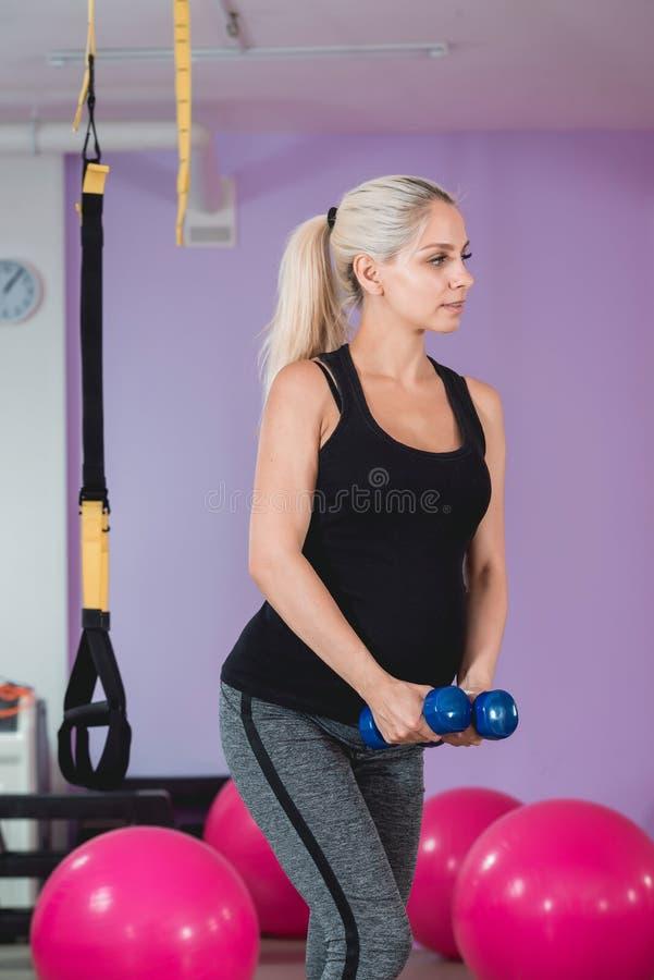 在健身房的孕妇立场,拿着她的重量与可爱的眼力的9个月和做在肩膀的锻炼和 免版税库存照片