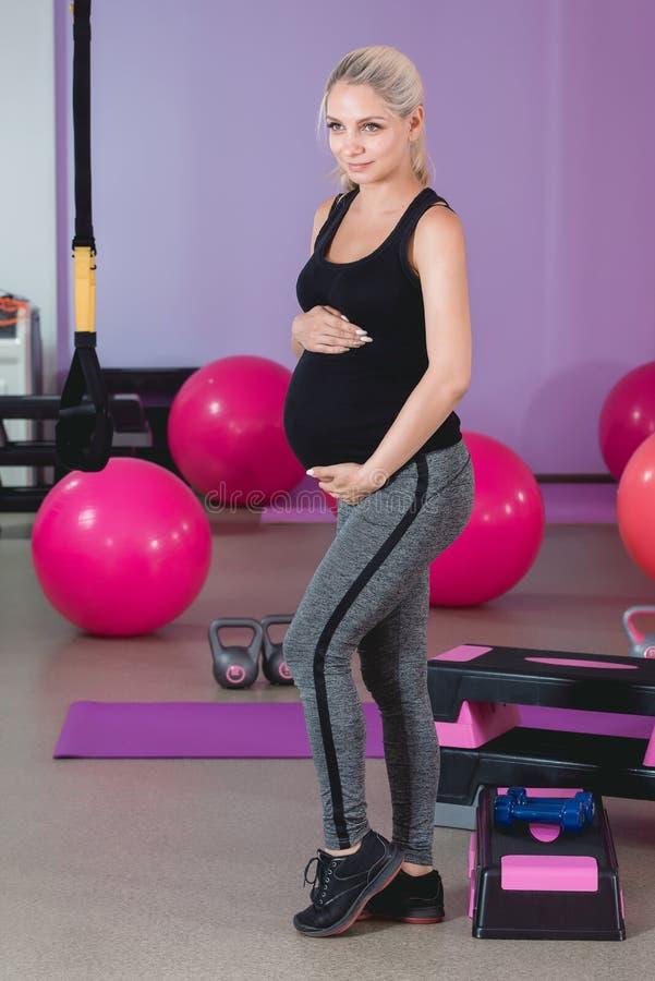 在健身房的孕妇立场,握她的腹部与可爱的眼力的9个月 免版税库存照片
