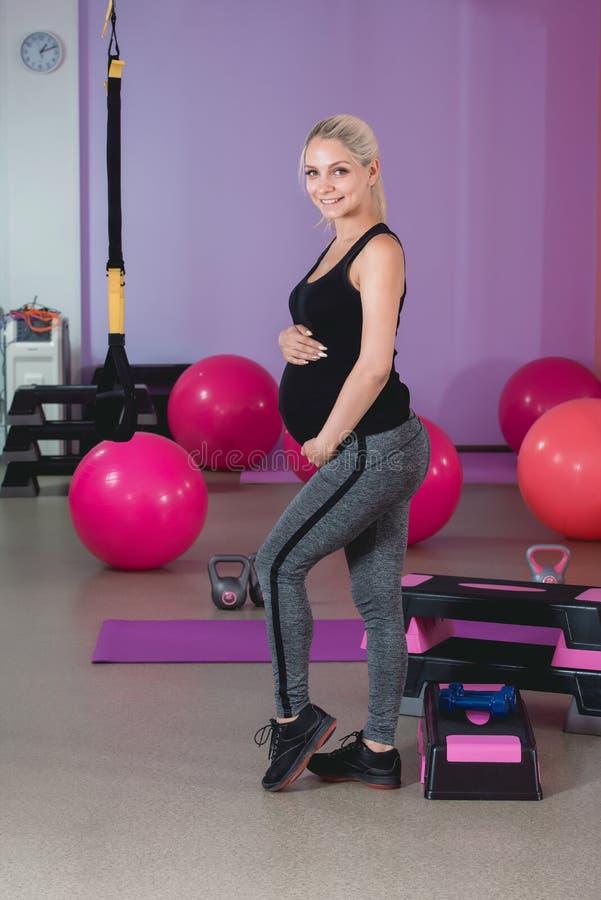 在健身房的孕妇立场,握她的腹部与可爱的眼力的9个月 库存照片
