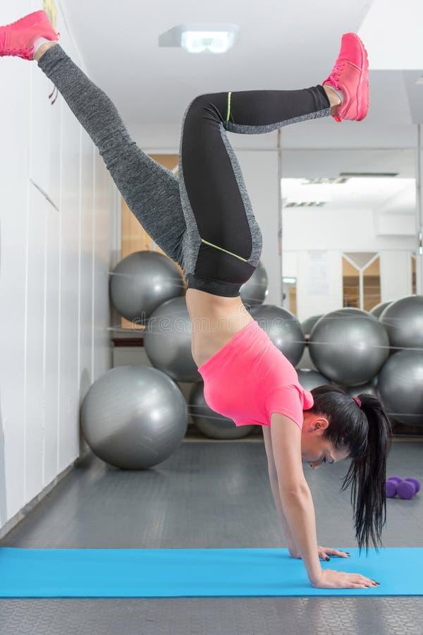 在健身房的少妇尝试的手倒立 图库摄影