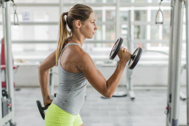 在健身房的少妇训练 免版税库存图片