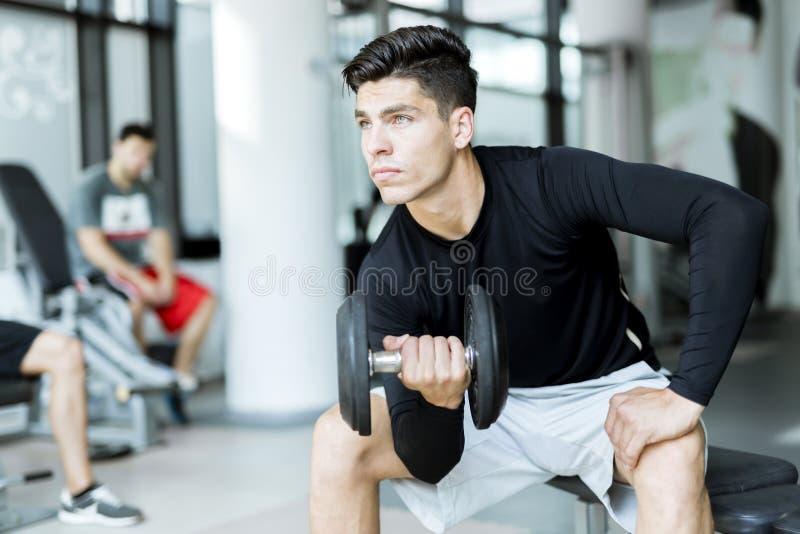 在健身房的年轻人训练 免版税库存图片