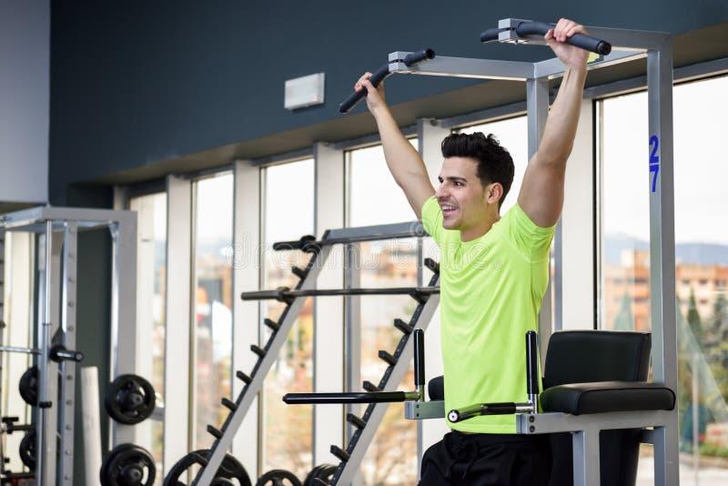 在健身房的年轻人适合的人佩带的运动服训练 库存图片