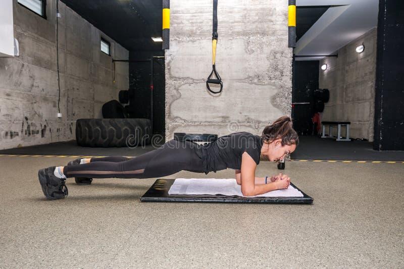 在健身房的年轻有吸引力和活跃女孩锻炼板条锻炼力量的和适应与杠铃在她的重量板材 图库摄影