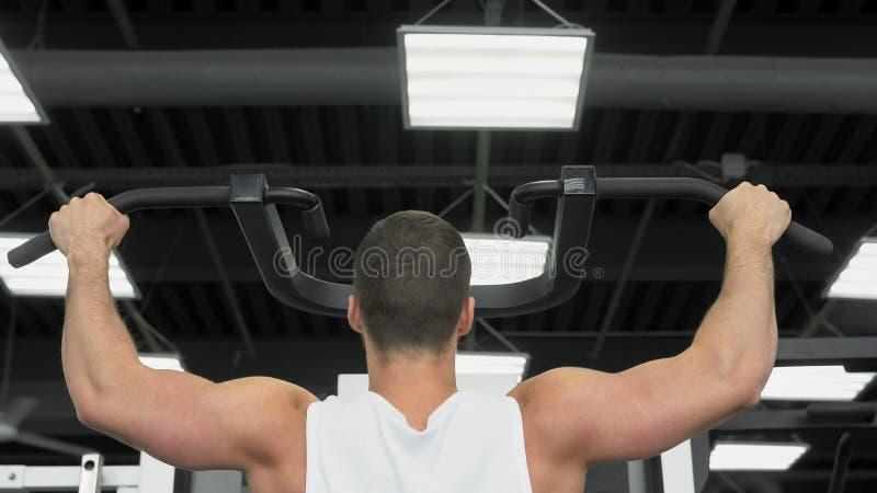 在健身房的年轻肌肉人火车 重量训练的运动员 免版税图库摄影