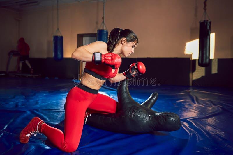 在健身房的年轻运动女孩战斗机火车 免版税库存图片