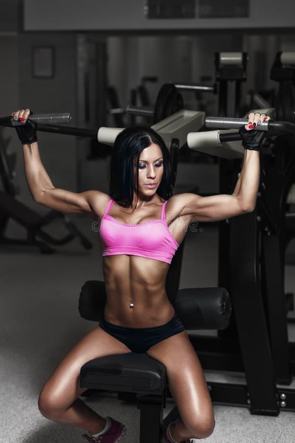 在健身房的性感的运动员妇女推力 浅黑肤色的男人执行一exerci 库存照片