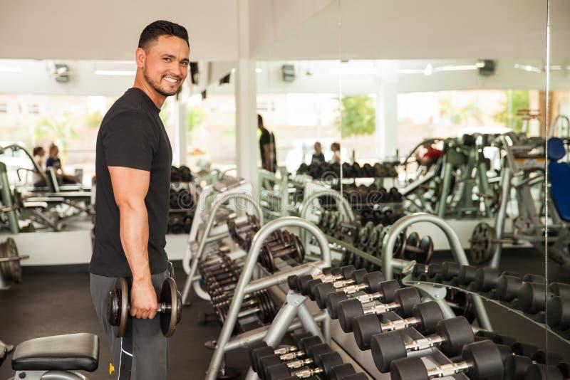 在健身房的拉丁年轻人举的重量 免版税库存照片