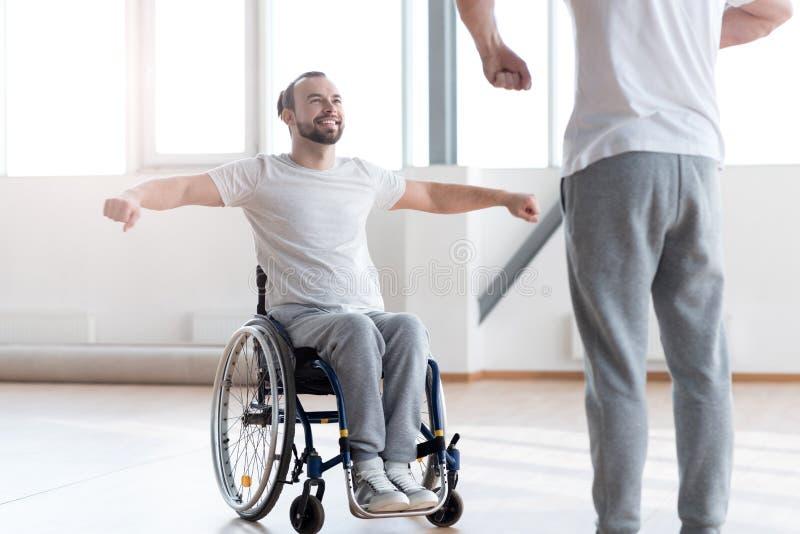 在健身房的殷勤残疾人训练与骨科医师 库存照片