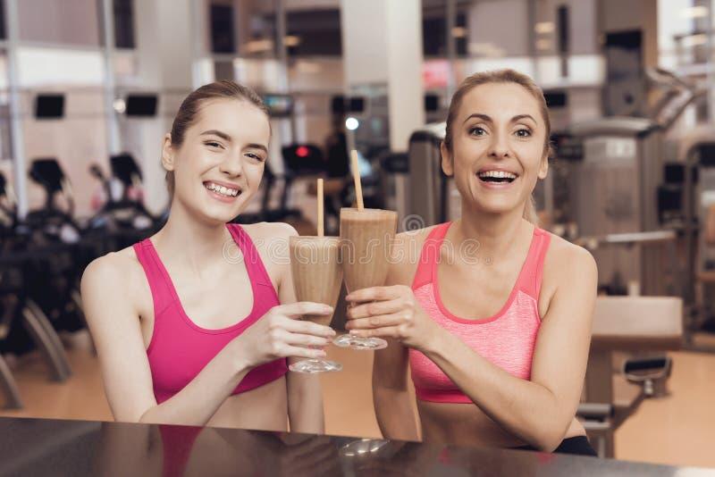 在健身房的母亲和女儿饮用的蛋白质震动 他们看起来愉快,时兴和适合 免版税图库摄影
