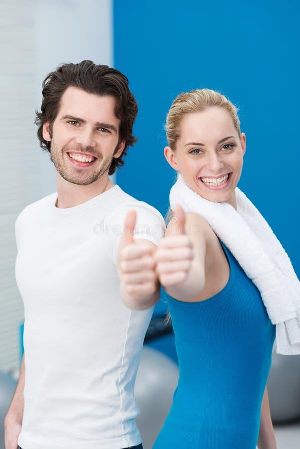 在健身房的热心年轻夫妇 免版税库存图片