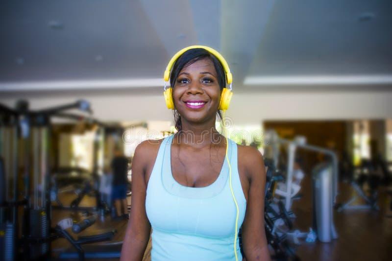 在健身房的生活方式画象年轻愉快和有吸引力美国黑人妇女训练快乐在听到音乐w的健身俱乐部 免版税图库摄影