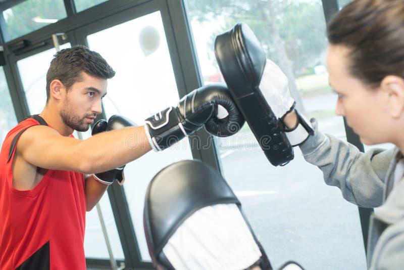 在健身房的男性运动员训练拳击技能 库存照片