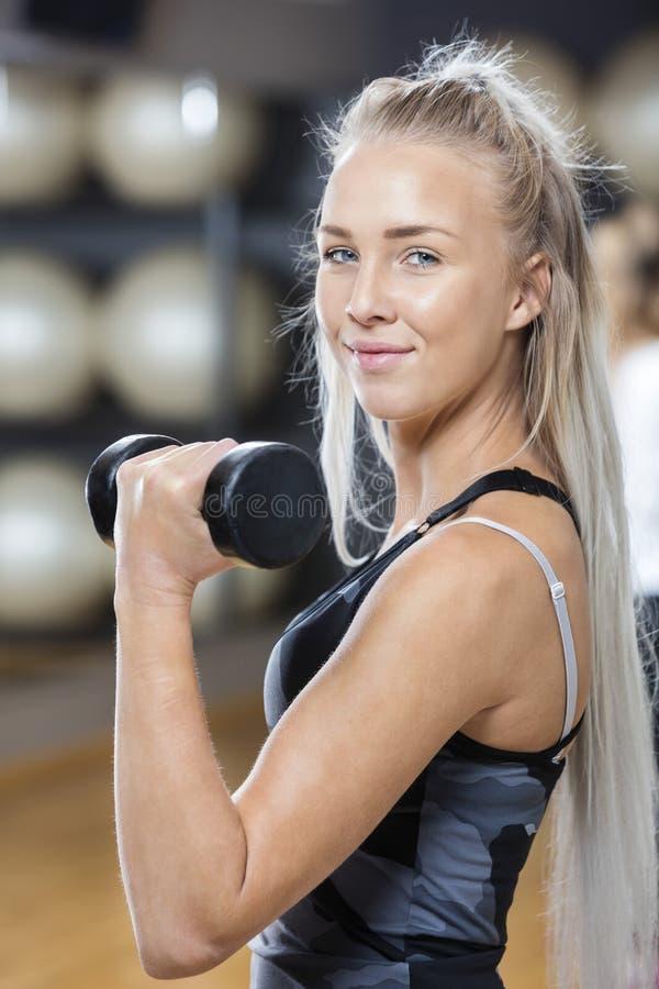在健身房的确信的少妇举的哑铃 免版税库存图片